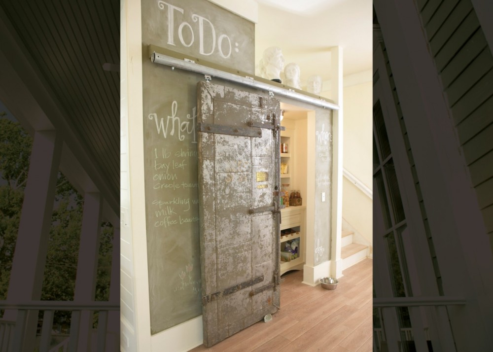The rustic, sliding pantry door was salvaged from an old New Orleans bank safe. The chalkboard wall is perfect for recording recipes, reminders, grocery lists, and kids' drawings.