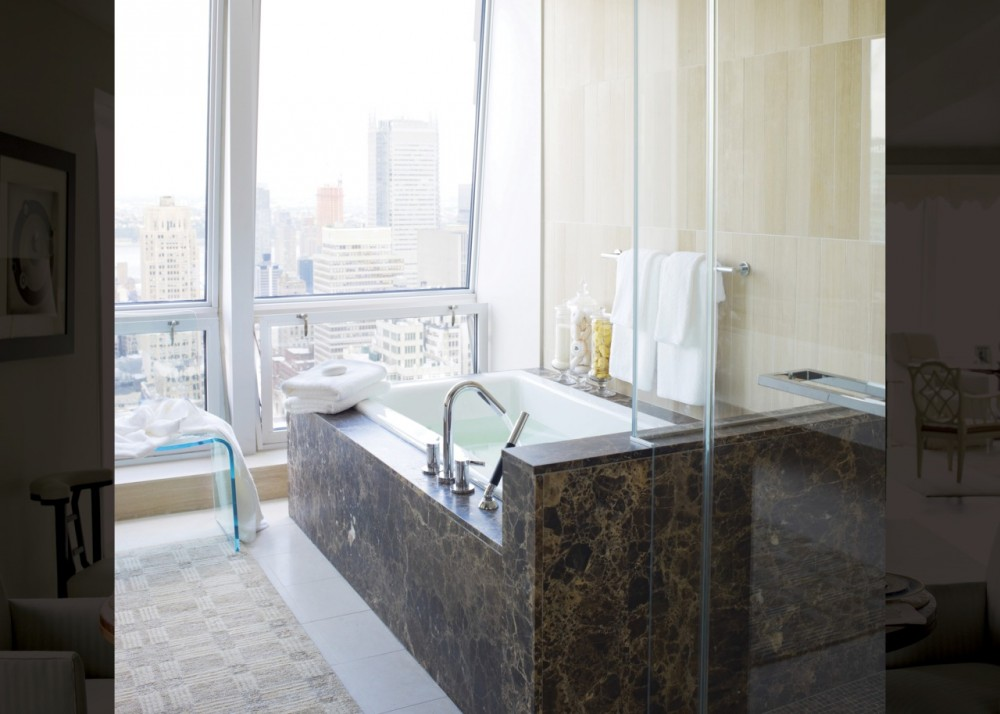 Tea-for-Two BubbleMassage air bath    Stillness bath faucet    Shift Ellipse handshower    Richly veined marble and muted tones lend this master bathroom a stately feel, while floor-to-ceiling windows draw gazes to expansive views of Manhattan.